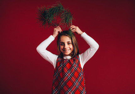 Smiling girl holding twigs to her head