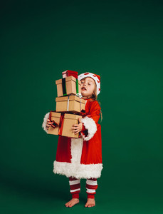 Kid dressed as santa carrying gifts