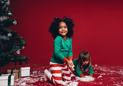 Two kids playing with artificial snow beside a christmas tree