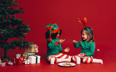 Kids eating cookies sitting beside a christmas tree