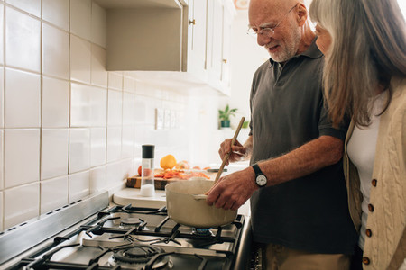 Senior couple cooking food together at home