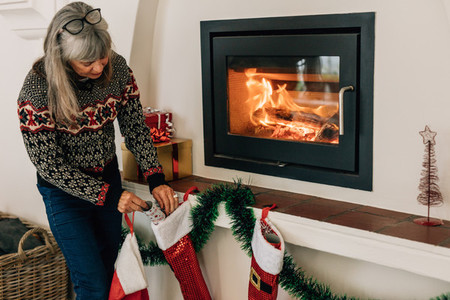 Senior woman decorating home for christmas