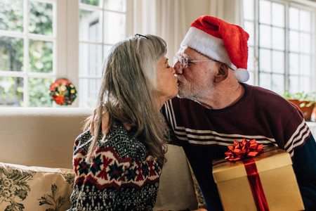 Happy senior couple kissing each other celebrating christmas