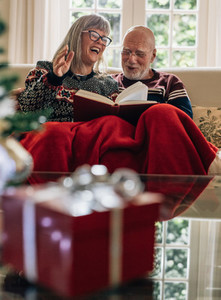 Senior couple spending time together reading a book