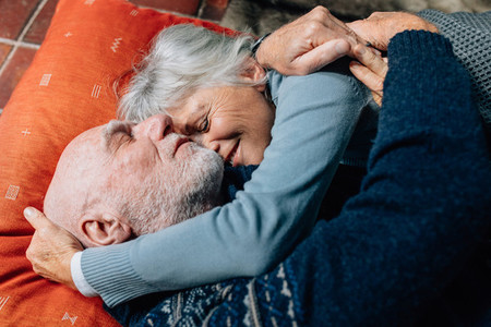 Senior couple expressing love embracing each other lying on floo