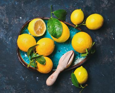 Freshly picked lemons with leaves in blue ceramic plate