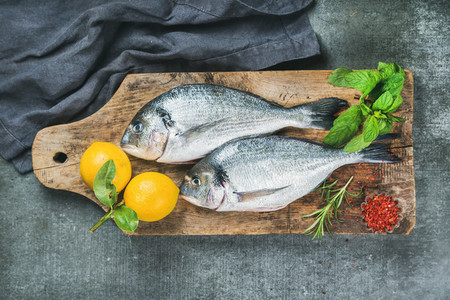 Uncooked sea bream or dorado fish with lemon