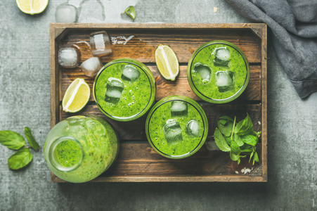 Fresh green smoothie with ice cubes  mint  lime in tray