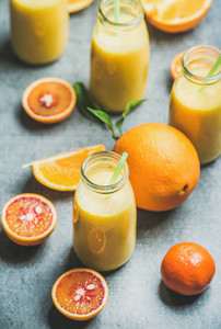 Healthy yellow smoothie in bottle over concrete background
