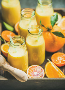 Healthy yellow smoothie in bottles in wooden box