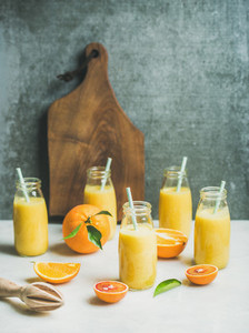 Healthy yellow smoothie with citrus fruit on light table