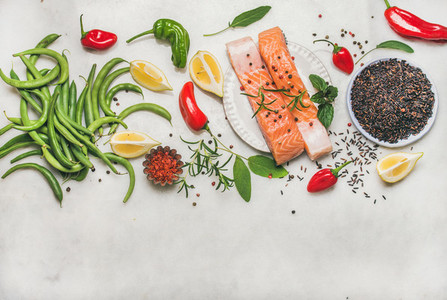 Flat lay of raw salmon fish fillet steaks with vegetables  greens