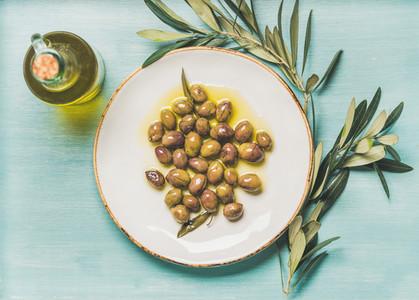 Pickled green olives  olive tree branch  virgin oil  blue background