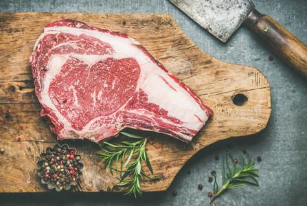 Raw uncooked beef steak rib eye on board with seasoning