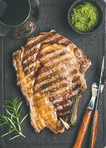 Grilled hot rib eye beef steak on bone and red wine