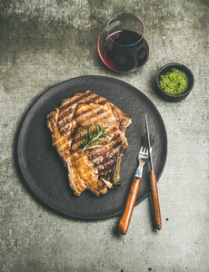 Grilled hot rib eye beef steak with red wine in glass