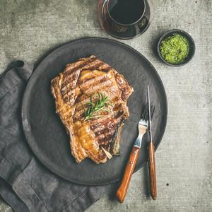 Flat lay of Grilled rib eye beef steak on bone  square crop