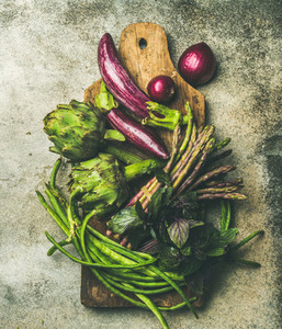 Flat lay of green and purple vegetables on board grey background