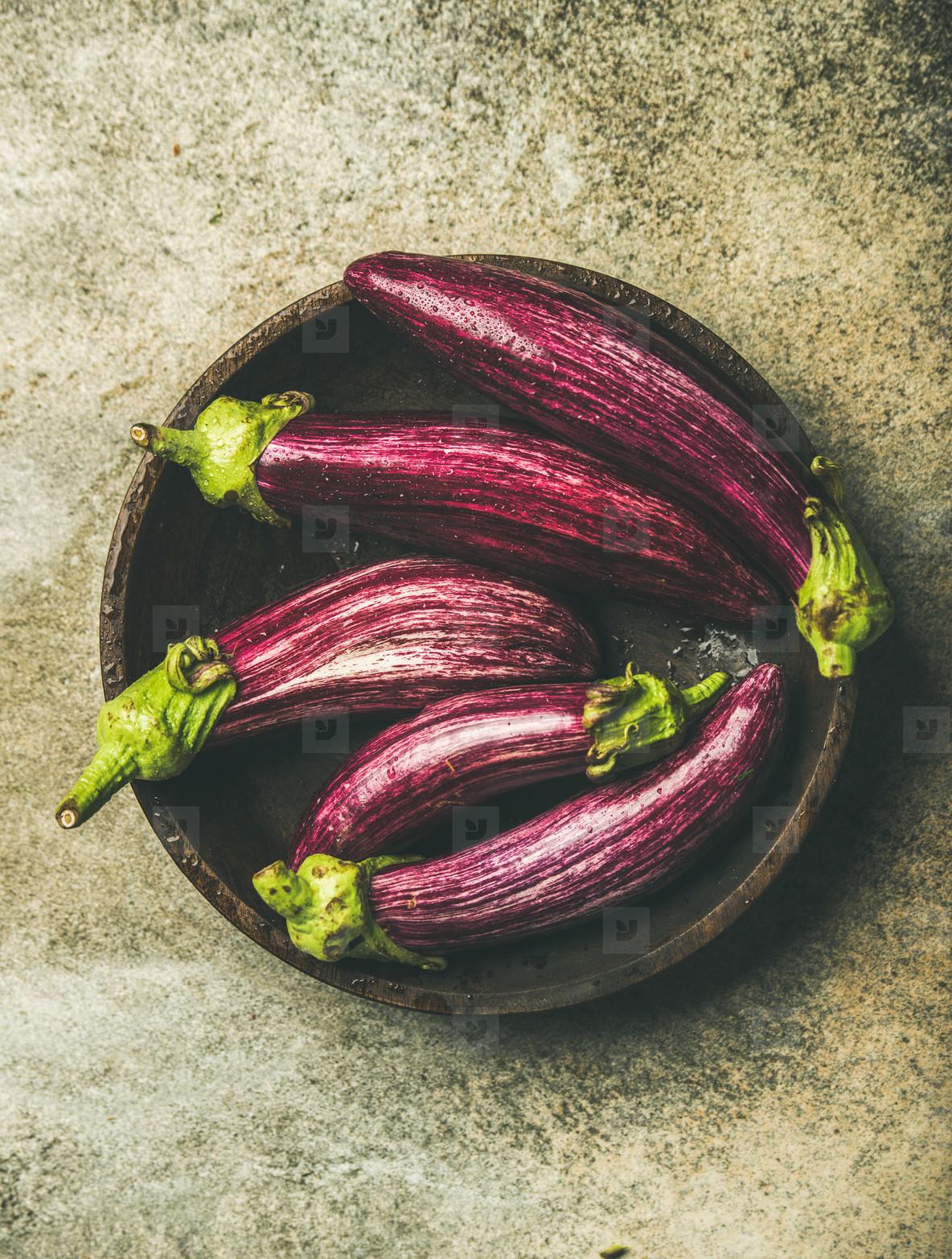 Flat lay of fresh raw Fall harvest purple eggplants or aubergines