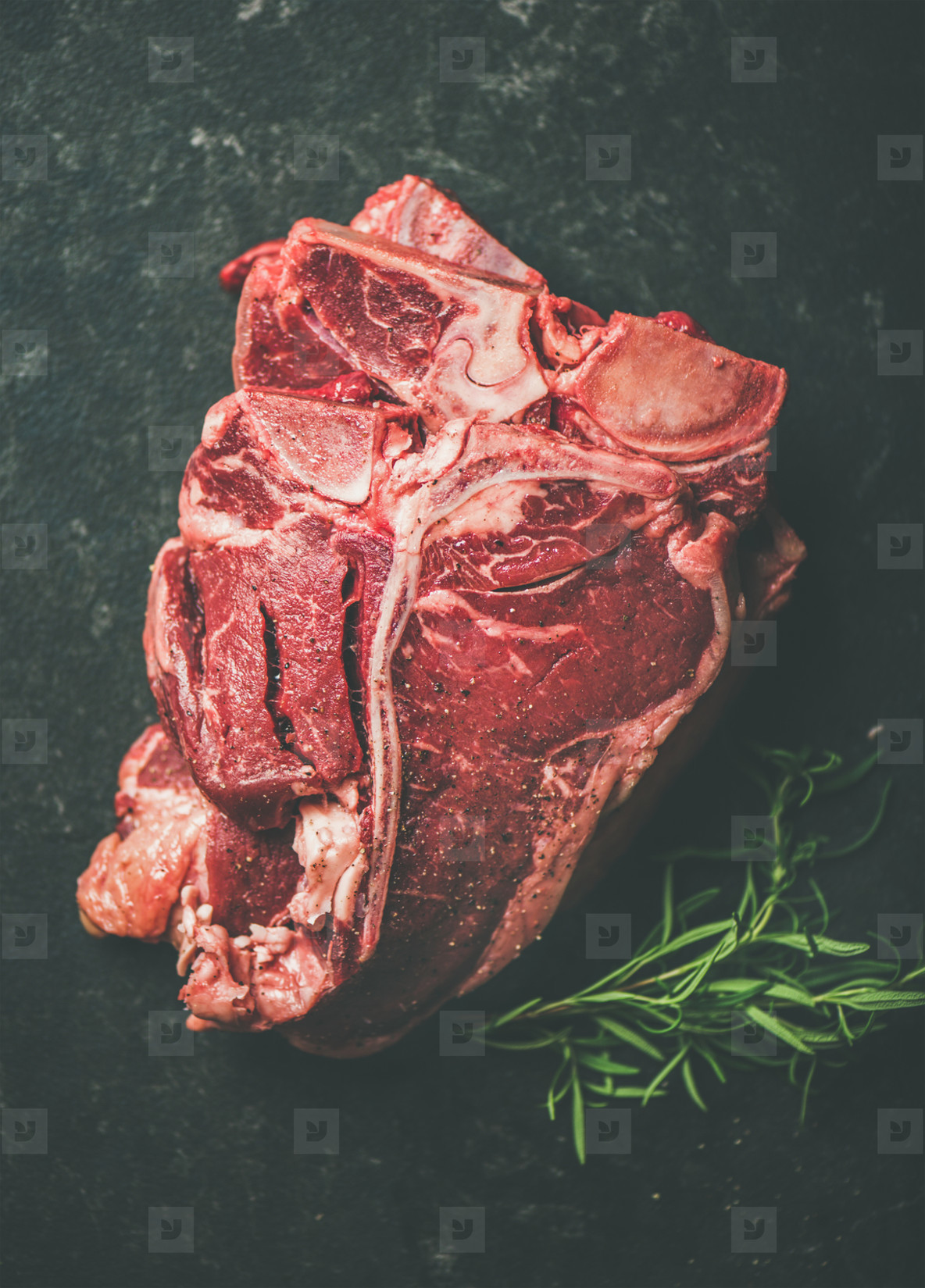 Raw beef meat t bone steaks with rosemary placed in stack