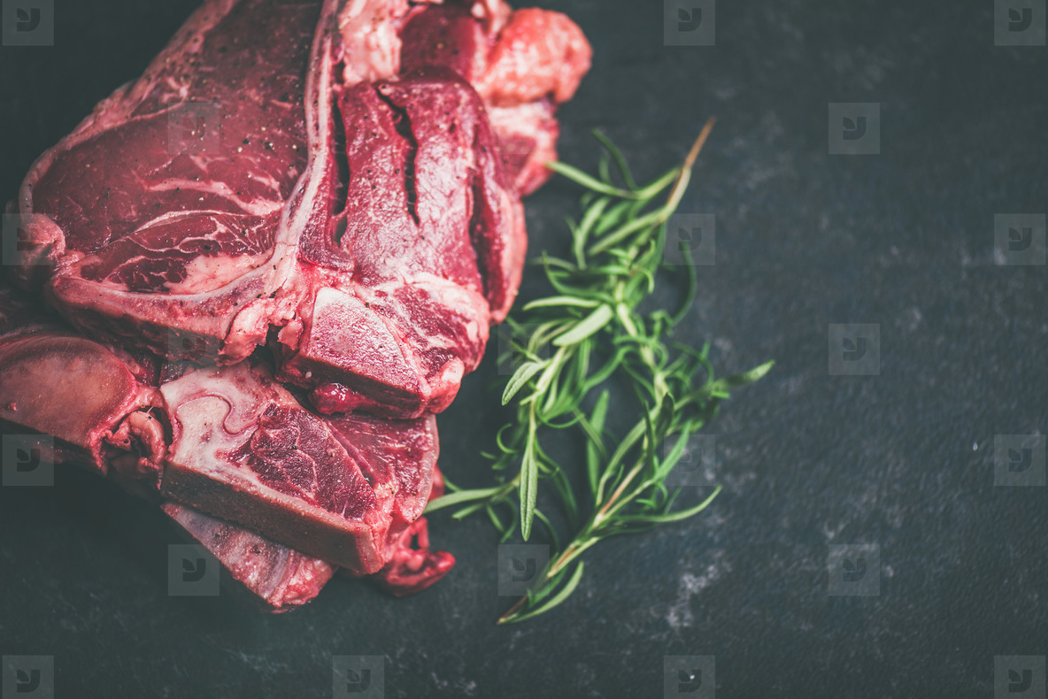 Raw beef meat t bone steaks with rosemary and spices
