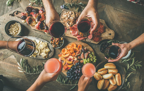 People having party sitting at table set with wine snacks