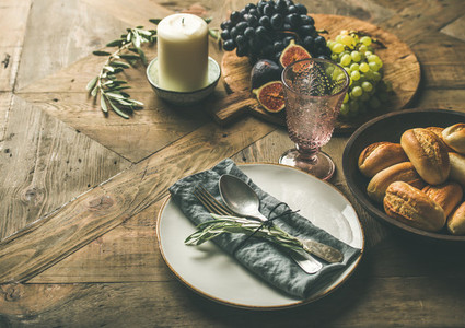 Plate with linen napkin  fork  spoon  glass  candle  fruits
