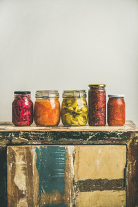 Autumn pickled vegetables in jars placed in line  copy space