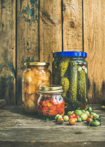 Autumn seasonal pickled vegetables and fruit in jars copy space