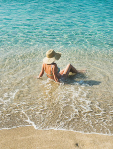 Senior woman tourist in bikini sitting at clear sea waters