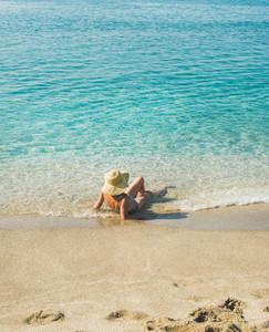 Senior woman tourist in bikini lying at clear sea waters