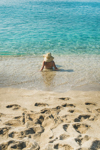 Senior woman tourist in hat lying at clear sea waters