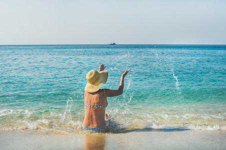 Senior woman tourist in bikini sitting on sand enjoying sea