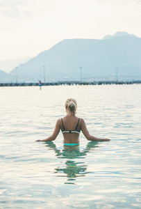 Young woman standing in still morning sea waters in Alanya