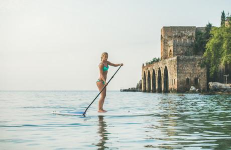 Young beautiful slavian woman tourist practicing paddle boarding  Alanya