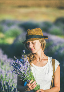 Girl wearing straw hat with a bouquet of lavender flowers
