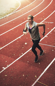 Young active sportswoman running on stadium