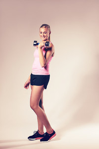 Woman smiling looking at dumbbell