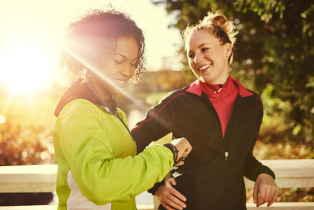 Two sportswomen in park smiling and looking at watch