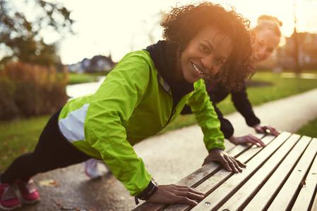 Two smiling sportswomen doing push ups