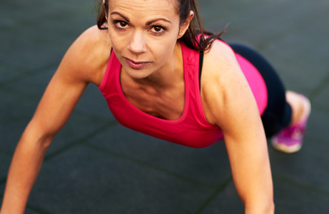 Woman looking at camera in a push up stance