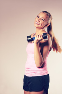 Woman smiling at camera holding dumbbell