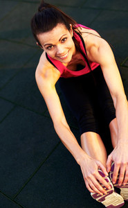 Above view of woman stretching hamstrings on floor