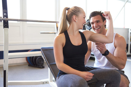 Playful Couple Checking Bicep Muscle Size in Gym