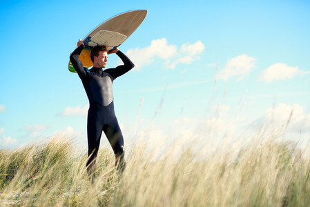 Strong young surfer crossing a sand dune