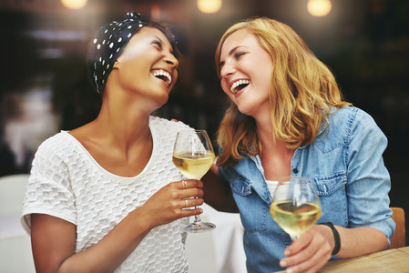 Two young female friends celebrating and laughing