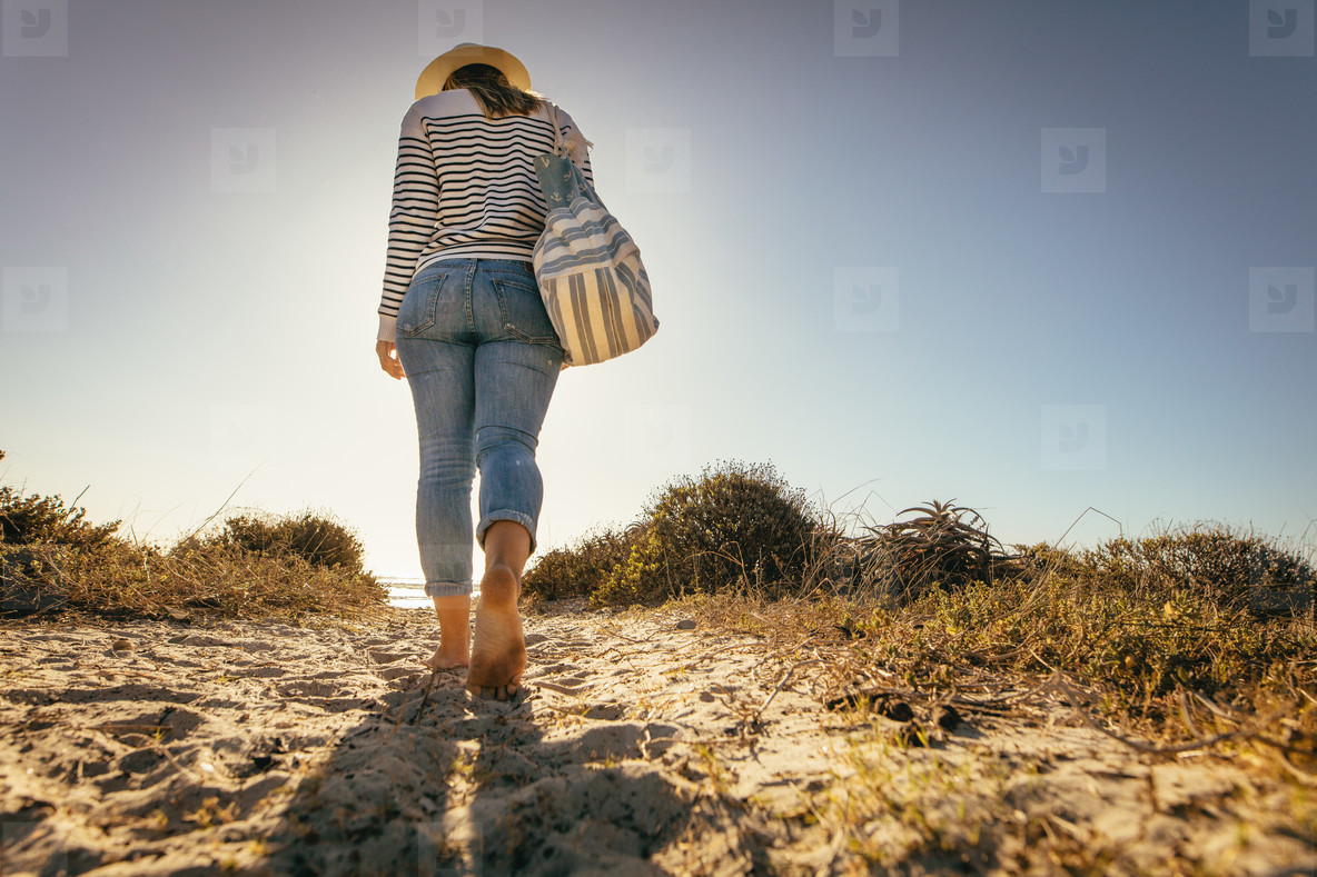 Rear view of a woman walking on beach sand