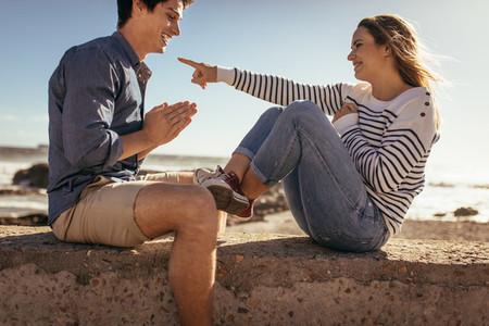 Couple sitting on sea wall having fun