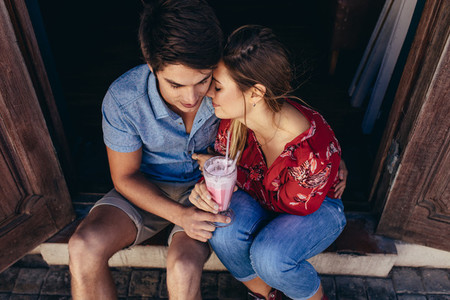 Romantic tourist couple sitting at the doorstep with a milkshake