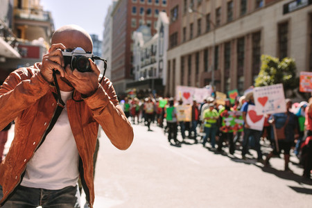 Man shooting pictures of rally on road